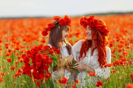 Little girl with redhead mother in white dresses and wreathes poses with bouquet of poppies on poppy field at warm summer sunset