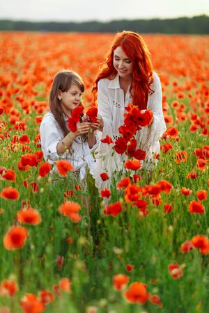Little happy girl with redhead mother in white dresses makes wreath on poppy field at warm summer sunset Stockfoto