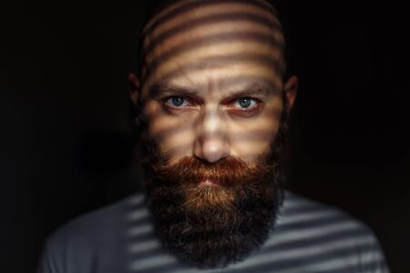 Close-up portrait of middle aged brutal bearded man with expressive eyes and striped shadows on his face Imagens