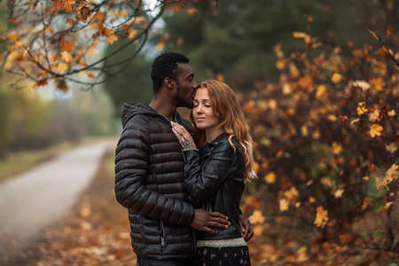 Happy cute Interracial couple posing in blurry autumn park background, black man and white redhead woman
