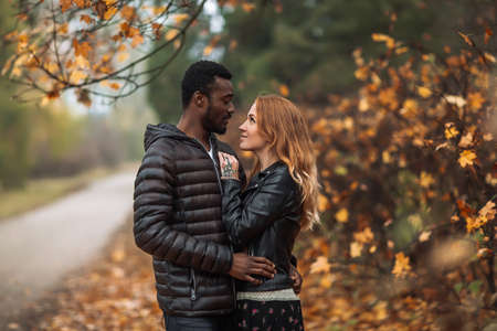 Happy cute Interracial couple posing in blurry autumn park background, black man and white redhead woman 免版税图像 - 151144352