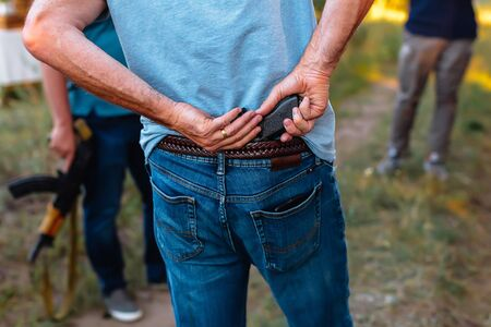 man hides a pistol behind his back under the belt of jeans with group of criminals