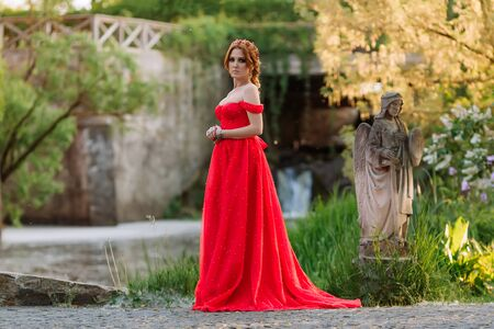 Attractive redhead tattoed woman in long red dress posing near the castle 스톡 콘텐츠