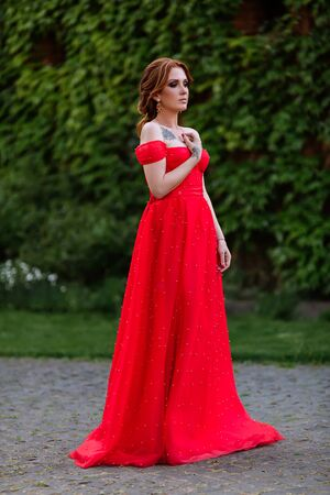 Attractive redhead tattooed woman in long red dress and diadema on blurred medieval castle background