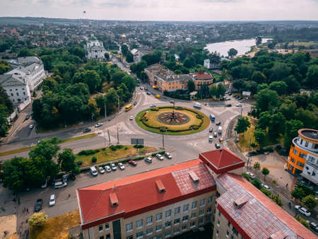 Aerial view of roundabout road with circular cars in small european city at summer afternoon, Kyiv region, Ukraine