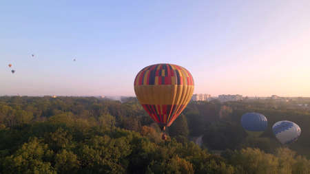 Aerial drone view of colorful hot air balloon flying over green park in small european city at summer sunrise, Kiev region, Ukraine