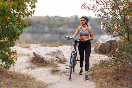 Fit young woman wearing sportswear standing with her bicycle on rocky background
