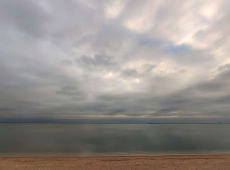 Nice cold autumn seaside background with a desert beach, a calm sea, a cloudy sky and sea mist in the horizon, Ukraine, Europe Imagens