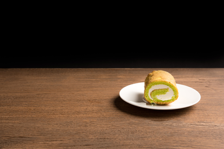 green tea cake roll on wood table with black background. Фото со стока