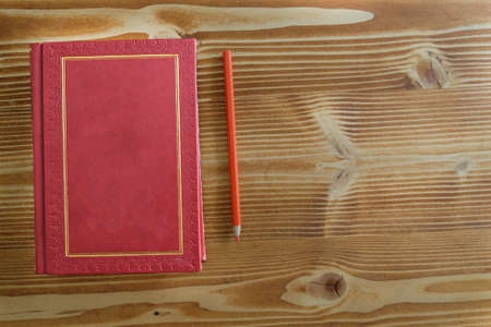 antique red gilded book on the old wood table with colorful pencils for distance learning