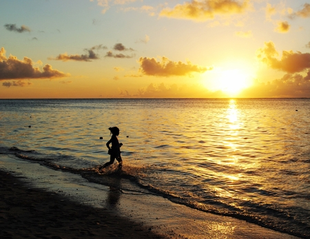 A girl playing in the golden waters reflected by the setting sun.