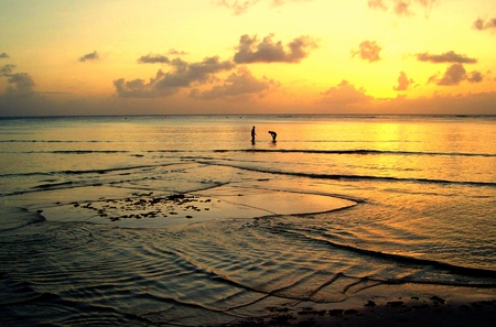 The sunset casts golden ripples in the waters of Saipan, CNMI