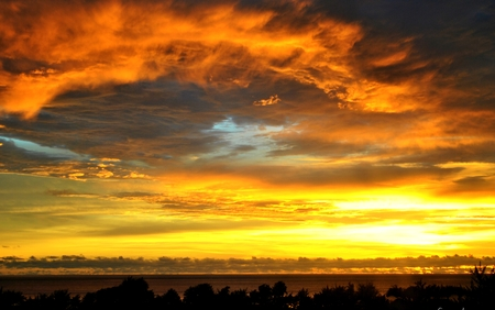 Tongues of Fire -Tongues of fire in the clouds as the sun sets in Saipan, Northern Mariana Islands Stock Photo