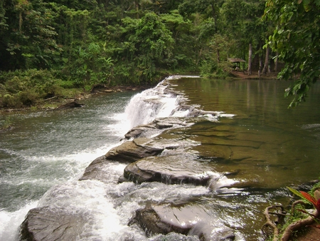 lowest tier of Tinuy-an Falls, Surigao, Philippines Water flows over the rocky beds and down into the last tier of the multi-tiered Tinuy-an Falls
