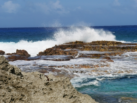 Huge waves at Swimming Hole, Rota Northern Mariana Islands Giant waves splash against a platform of rocks at the Swimming Hole in Rota