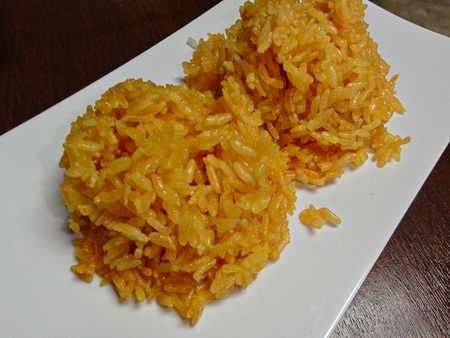 Steamed yellow rice in a white plate Steamed yellow rice is one of the traditional foods in the Micronesian islands. Rice is cooked and mixed with onion, olive oil, turmeric, garlic power, black pepper and salt for flavorings. Stock Photo