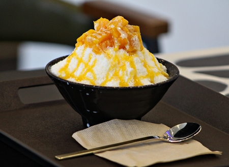 Bingsu (ice snow) topped with ripe mango, side view Bingsu is a popular Korean dessert made of snow-soft ice shavings and various sweet ingredients like  condensed milk, fresh fruits, syrup, cereal flakes and more, topped with icecream and yogurt.