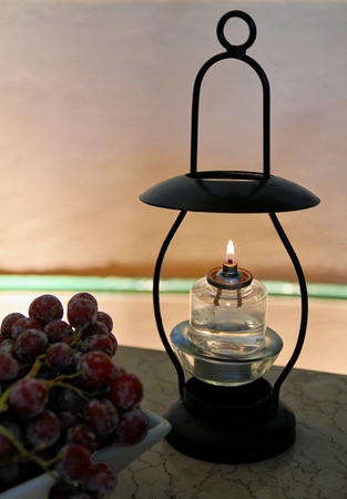 adds: Oil lamp at dinner table Lighted oil lamp with cover adds art to a table arrangement. Stock Photo