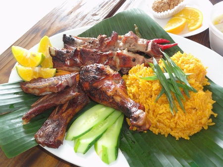 Chamorro beef and chicken barbeque meal with yellow rice in banana leaves Authentic Chamorro favorite cuisine of beef and chicken barbeque served with yellow rice, cucumber and lemon slices. Stockfoto