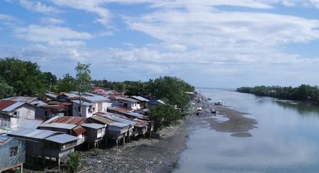 Bangkerohan 川、海から来ると潮土地はダバオ市で Bankerohan 川、高床式の家の下に消えてダバオ市で竹馬に乗って住宅します。 写真素材