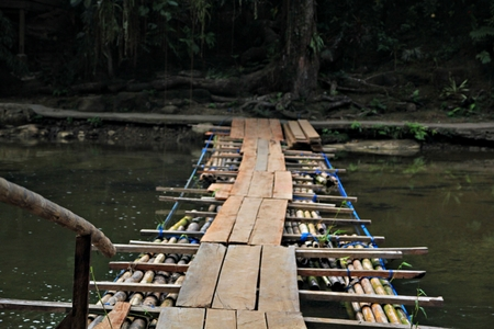 Floating wooden and bamboo bridge A raft made of bamboo and pieces of wood serve as a bridge from one bank of a river to the other in the Philippines