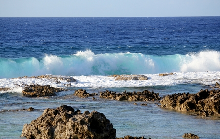 Long rolling waves  splashing toward rocky shores Foaming waves rolling toward the corals and rocks in the shorelines