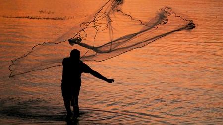 Silueta de un pescador de pesca de red de pesca un pescador de la pesca de una pesca de la vendimia se encuentra contra la isla de la puesta del sol Foto de archivo - 80001018