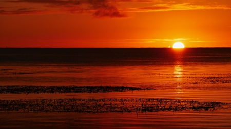Uma rodada completa lentamente desaparece no mar, Saipan Pôr do sol incrível em Saipan é uma coisa regular e uma das características mais marcantes da ilha. Foto de archivo - 79886056