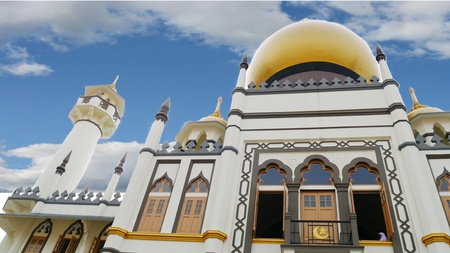 indo: Upward view of Masjid Sultan Mosque with clouds, Kampong Glam, Singapore Masjid Sultan Mosque in Kampong Glam features indo-saracenic revival architecture and is one of the top tourist destinations in Singapore.