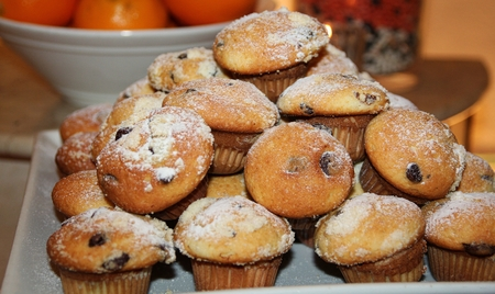 Pile of raisin muffins  A pile of freshly baked muffins with raisins, heaped in a tray