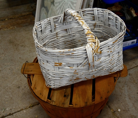Wicker basket with peeling white paint, on top of a round wooden bucket