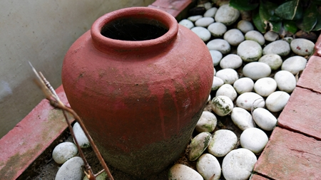 One big red earthen jar on the ground surrounded by smooth white stones