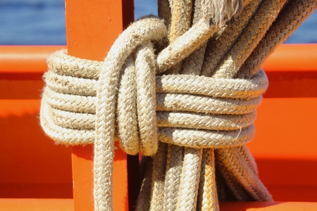 Sturdy white ropes tied in a secure tight knot against a wood post Banco de Imagens