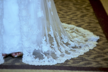 Hem of a white wedding dress trailing in the carpet, with the bride's feet showing up