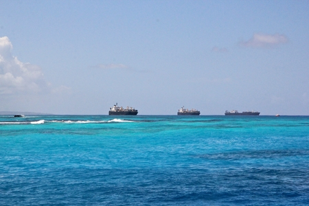 Ships and fishing boats moored beyond the reef in the blue sea at a tropical island Banco de Imagens