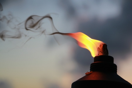Fire and smoke rises from a lighted tiki torch