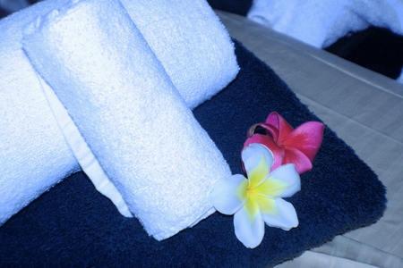 Massage table with rolls of white towels and plumeria flowers Imagens