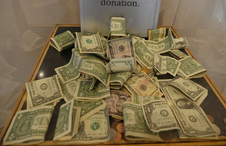 Assorted United States dollar bills and coins in a donation box