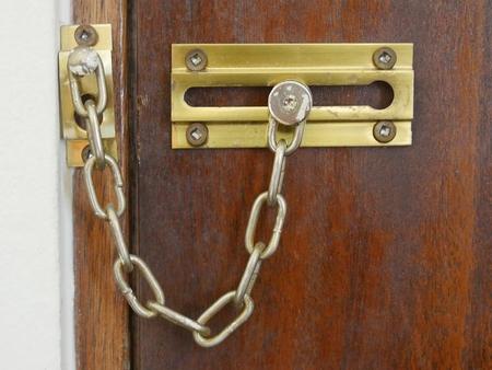 Old safety chain lock on door Stock Photo
