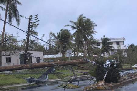 The day after a typhoon hit a tropical island uprooting electric power posts and trees, leaving damaged houses and roads Stockfoto
