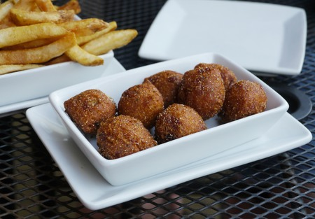 Deep fried browned hush puppies served on white plates, with blurred French fries in the background