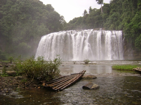 Front view of Tinuy-an Falls with a bamboo raft in the foreground. Tinuy-an Falls is popularly known as as the Niagara Falls of the Philippines in Surigao del Sur, Philippines