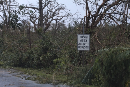 Day after a typhoon in a tropical island, with trees damaged and road sign turned upsidedown