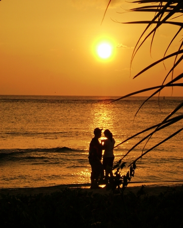 Unrecognizable couple silhouetted at the beach at sunset Stock Photo