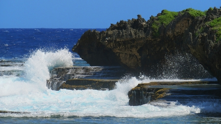 Foaming waves crashing against beautiful cliffs and stones at a tropical beach 写真素材