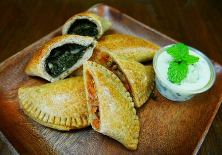 Empanadas stuffed with healthy vegetables served on a wooden plate, and dipping with basil leaves