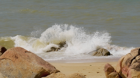 Waves roll in against the rocks in the seashore.