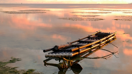 A bamboo raft floats bathed in the golden reflections of a tropical sunset. 版權商用圖片