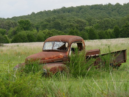 Rusty old pickup truck with shattered windshield parked in a grassy patch, with a for sale sign 免版税图像