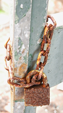 Close up of a very rusty chain held fast by an equally rusty padlock